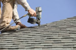 Man working on roof with nail gun. Culpeper Roofing 540-680-3612